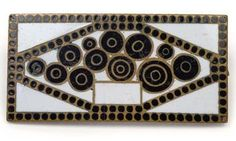 Josef Hoffmann, brooch, designed c. 1910, executed by Johann Souval for the Wiener Werkstätte, gilt brass and polychrome enamelled with stylised flower, on the reverse impressed monogram WW, length 3.2 x 1.5 cm, (B).   [An archive photograph is preserved in the WW Archives at the Austrian Museum of Applied Arts (ÖMAK), Vienna with inventory no. WWF 89-20-1.]  |  SOLD $1,650 Nov. 3, 2015