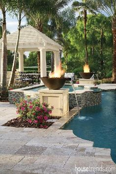 Fire bowls around a swimming pool double as water features