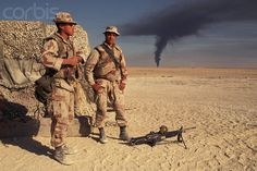 Two US Marines of the Third Battalion watch black smoke from an oil fire ascend from the horizon. As Iraq's forces retreated from Kuwait, Saddam Hussein ordered the burning of Kuwait's oil fields. 1990