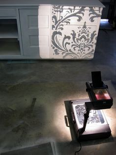 Transferring a fabric print to transparency and painting it on furniture. Check out her post...the before and after pics are great...you could also do this on canvas - fabuloushomeblog.com