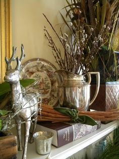 Love this rustic mantel inspiration! Silver pitchers and vessels (even julep cups!) filled with greenery, branches, pinecones and more. Via Three Pixie Lane. #Christmas #decor