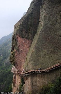 Chinese workers balance on planks with no ropes as they build road up a mountain | Daily Mail Online
