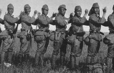 Japanese army soldiers take a moment to relax and massage each other's shoulders, somewhere in China, late 1930s.