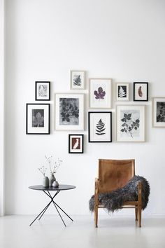 Modern living space with a vintage leather chair, lamb throw, and gallery wall