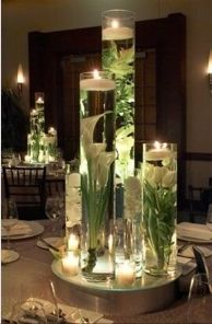Glue fake flowers to the bottom of a tall vase (or to stones you could drop in), fill with water, and top with a floating candle. Gorgeous and you could use any color to fit the room you put it in :)