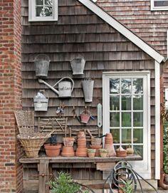 Tabla de este trabajador de la madera de roble circa-1900 fue reclutado por el servicio como una estación para macetas, luego colgó cubos vintage y regaderas en el muro exterior de esta casa.