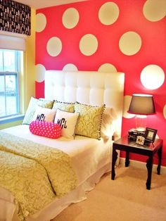 Love this pink statement wall, with giant white vinyl polka dots! And the contrast with the bedspread.