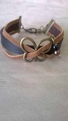 CREA 42 : Bracelet fabriqué avec 2 lanières en suédine caramel et simili cuir noir. Avec au centre un papillon en bronze avec 2 petites perles.