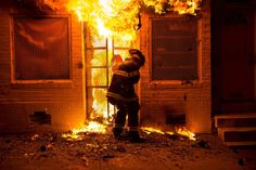 A firefighter uses a saw to open a metal gate while fighting a fire in a convenience store and residence during clashes after the funeral of Freddie Gray in Baltimore, Maryland.