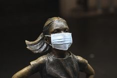 """A surgical mask is placed on the """"Fearless Girl"""" statue outside the New York Stock Exchange on Thursday, March Wall Street, Black Swan Event, Pictures Of The Week, The Guardian, In This Moment, World, March, Thursday, Country"""