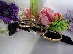 True Vintage Set of Three Bangle Bracelets. The  First Bangle Bracelet is made of Goldtone Metal.The Other is Silvertone. The third bangle is made of Goldtone Metal. The Set is Priced Perfectly and you get Free Shipping to the United States. CCCsVintageJewelry.com
