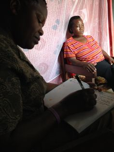 Our first interview in a student's home; Resty, who works with Cari, served as interpreter for us.  She is writing down what the mother is saying in my production notebook.