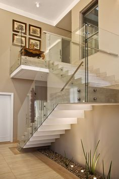 A escada com degraus em mármore Travertino Romano Bruto e guarda-corpo de vidro
