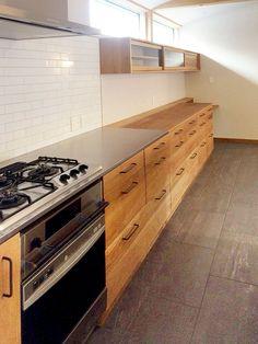 オークとタイル、ステンレスのキッチン。 引出しの高さを合わせているので美しく見えます。 収納はたっぷりで作業台…
