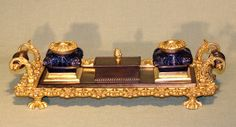 An early 19th century Regency period bronze and ormolu Pentray having unusual blue glass inkwells supported on scrolled border base with bronze turned handles.