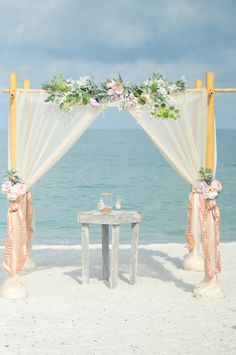 Romantic shades of pink and ivory beach wedding arbor.