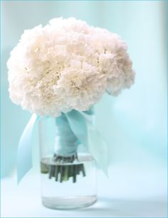 Simple arrangement of white (or ivory) carnations wrapped with robin's egg blue ribbon in a cylinder vase.  Inexpensive table decor for a baby shower
