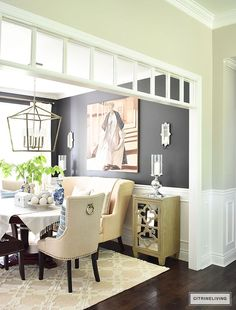Sophisticated and elegant dining room with transom details. Black walls painted in Cracked pepper by Behr Paint. Neutral decor with layers of blue and white pottery. Upholstered chairs with antique brass nailed trim are elegant and refined. Large scale la
