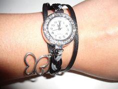 silberfarbene Uhr auf geflochtenem Lederband in schwarz und grau mit kleinem Schmetterlingsanhänger.    Verschlossen wird das Uhrenarmband mit einem K