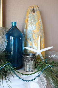 Beautiful beach themed Christmas decorations on a mantle.