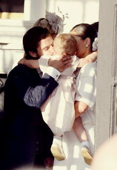 Princess Estelle, in the arms of her mother Crown Princess Victoria, getting a kiss from her uncle Prince Carl Philip