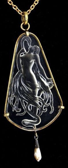 An Art Nouveau gilded metal and glass pendant in the style of René Lalique. The moulded glass depicting the figure of Eve and the serpent. Length 7.5cm. #ArtNouveau #pendant
