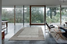 Courtyard House | spacious room with marble floor, beige rug + full glass wall