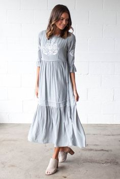 Bohme's Something Blue Midi Dress features a sage body with white embroidery, a full skirt, sleeve hem ruffle, and raw hem detailing.