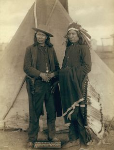 Two Oglala chiefs,         American Horse (wearing western clothing and gun-in-holster) and Red Cloud         (wearing headdress), full-length portrait, facing front, shaking hands in         front of tipi.-probably on or near Pine Ridge Reservation 1891. Photo: Grabill,         John C. H.