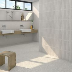 Modern bathroom with terrazzo style wall and floor tiles. His and hers sinks.