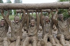 Paramilitary soldiers lift logs during a physical training in mud in Chuzhou, Anhui province, July 18, 2012. Picture taken July 18, 2012. (Photo by China Daily/Reuters)