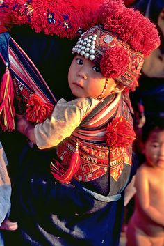 A Mien woman carries her baby on her back, secure in an exquisitely embroidered baby carrier. Mien women are masters of cross-stitch embroidery and spend much of their spare time stitching designs on their pants and on baby carriers and caps. Mien or Yao originated in China but over the past few centuries have migrated to Vietnam, Laos and northern Thailand where this photograph was taken. | © John Spies