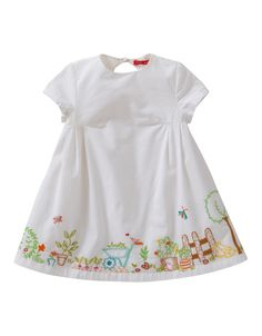 Bright white dress in sturdy cotton with a button closure on the back. The bottom of the dress has a playful embroidered Oilily vegetable garden.
