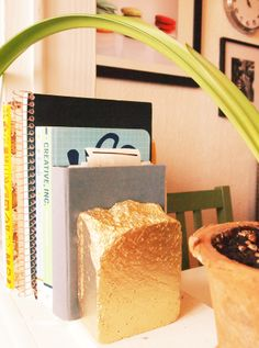Gold bar bookend. Chip one end of a brick, then paint it gold.