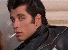 "John Travolta plays Danny Zuko, a classic greaser in the classic musical ""Grease."" The term ""greaser"" stems from the amount. John Travolta Young, Grease John Travolta, John Travolta Hairspray, Grease 1978, Grease Movie, Grease Boys, Grease Actors, James Dean, Danny Zuko Grease"