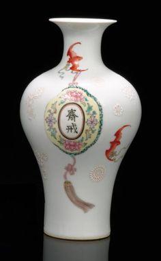 CHINE : Vase de forme balustre décoré en émaux de la famille rose de cinq chauve souris soutenant des médaillons à motifs de fruits, de lingzhis et de symboles shou, fleurs blanches en léger relief sur le fond. Porte au revers une marque jiaqing en zhuanshu en rouge de fer. XXème siècle. H: 23 cm