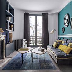 salon vert canard avec un canapé rétro avec des edredons et multiples coussins. Tables basses en boir design rétro et bibliothèque noire
