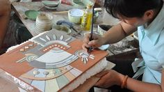 Painting intricate details on a bisque pot