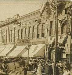 Celebration on Bismarck Street Flags, Banners, Carriages, Drug Store Sign. Between 1910-1919