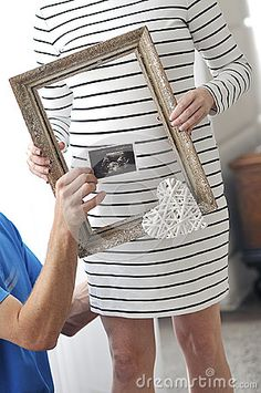 Pregnant woman holding a frame
