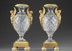 A pair of crystal ovoid Medici vases provided with gilt bronze sphinx shaped handles. Each vase is resting on a square base chiselled with friezes of palmette, above four half...