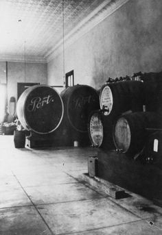 "Wine casks, labelled ""Port"" and wine jugs. Fisher/Fischer Wine Co., located on North Los Angeles Street, Anaheim, California."