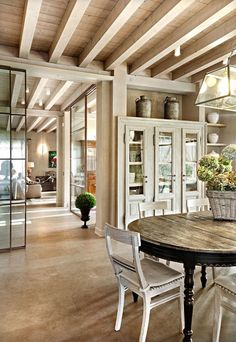 love the open space, glass sliding doors, beamed ceiling, & pale wood
