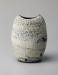 Lucie Rie: Flattened ovoid vase, Stoneware, mixed body material producing an integral blue and white spiral beneath the pitted glaze, mineral elements in the body material producing strong brown speckles. 7 7/8 in. (20 cm.) high, c.1965
