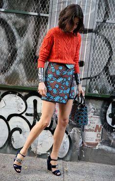 Leandra Medine com saia floral e suéter de tricô laranja.