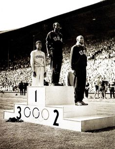 The medallists in the men's 100m stand to attention as the national anthem of the winner is played (L-R) Panama's Lloyd LaBeach (bronze), USA's Harrison Dillard (gold) and USA's Barney Ewell (silver) - Olympic Games, London - 31 July 1948