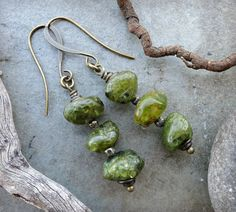 I created these rustic, earthy, apple green stone dangle earrings using tumbled peridot pebbles as the focus. As shown in the photos, they are smooth to the touch and gemmy leaf green in color, yet ar