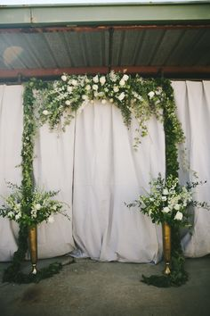green and white floral ceremony arch, photo by Ashley Kickliter http://ruffledblog.com/alabama-railyard-wedding #weddingceremony #weddingideas
