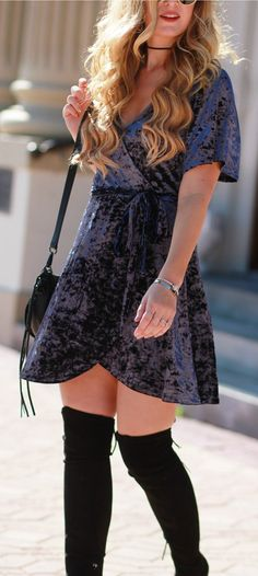 Cute holiday outfit idea with crushed velvet wrap dress, back over the knee boots, and round sunglasses