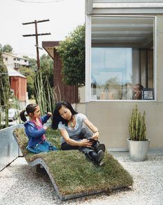 Téa gets mom ready for her close-up on the curvy nature-meets-industry chaise lounge of the architects' own design. The landscaping in front and out back is characterized by sturdy, resilient, and drought-resistant plants like bamboo and cacti, cultivated in galvanized steel planters.